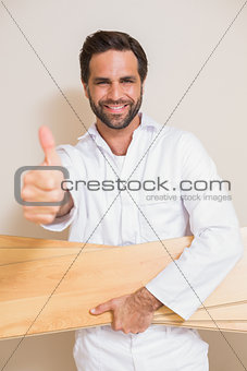 Carpenter holding planks showing thumbs up