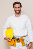 Handyman holding his yellow helmet in tool belt