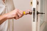 Man fixing the door handle with screwdriver
