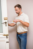 Man fixing the door handle with screwdriver