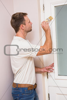 Painter painting the door white
