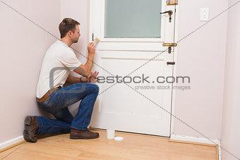 Painter painting the door white