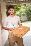 Delivery man smiling at camera offering parcel