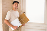 Smiling delivery man with box and clipboard