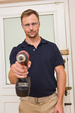 Handyman pointing power tool at camera