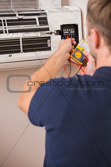 Focused handyman testing air conditioning