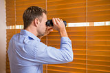 Man looking with binoculars through the blinds