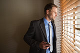 Man peeking through blinds while holding his phone