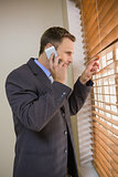 Businessman peeking through blinds while on call
