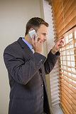 Businessman peeking through blinds while on call
