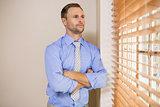 Serious businessman peeking through blinds