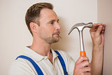 Man hammering nail in the wall
