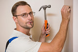 Handyman hammering nail in wall while looking at camera