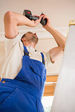 Handyman using a cordless drill to the ceiling