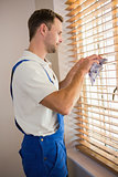 Manual worker cleaning blinds with a towel