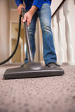 Close up a young man vacuuming