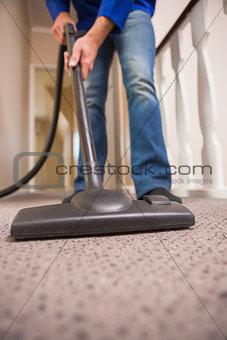 Close up a young man vacuuming