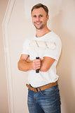 Smiling handyman posing while holding a paintbrush