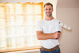 Smiling handyman posing while holding a paintbrush