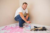 Man using paintbrush to paint wall blue