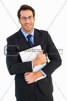 Smiling businessman holding his laptop looking at camera