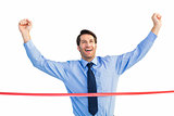 Happy businessman crossing finishing line