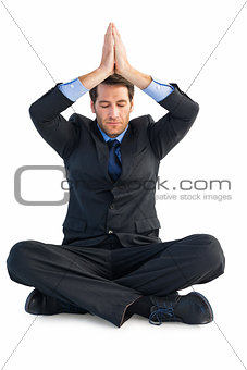 Calm businessman sitting in lotus pose with hands together