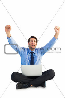 Businessman cheering with laptop sitting on floor