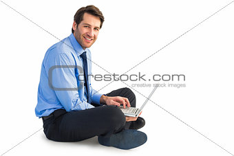 Smiling businessman sitting on floor working on laptop