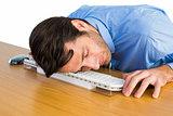 Businessman sleeping with his head on the keyboard