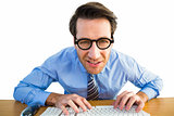 Businessman typing on his keyboard wearing glasses