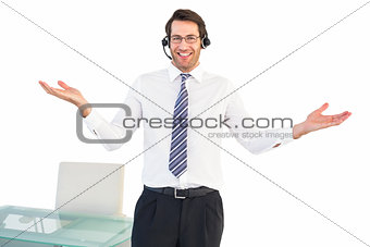 Smiling businessman presenting and wearing headphone