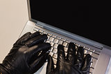 Close up of burglar hacking a laptop
