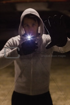 Man in hood jacket standing while making light with his phone