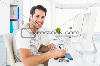 Casual man working at desk with computer and digitizer