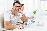 Man wearing glasses sitting at desk looking at camera