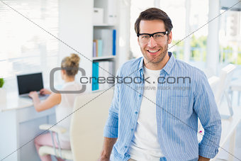Portrait of smiling photo editor wearing reading glasses