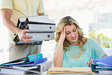 Stressed creative businesswoman with stack of files