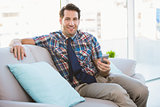 Happy man sitting on the couch sending a text message
