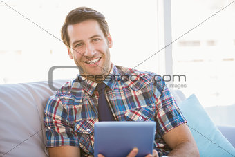 Portrait of man using tablet on the couch