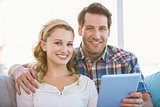 Couple using tablet pc on the couch while looking at camera