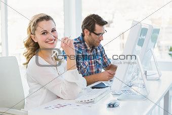 Casual photo editor working at desk smiling at camera