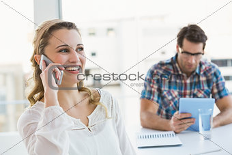 Blonde woman on the phone with her colleague behind