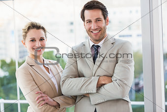 Business people posing with arms crossed smiling at camera
