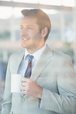 Handsome businessman holding cup of coffee