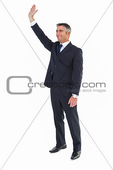 Smiling businessman in suit waving