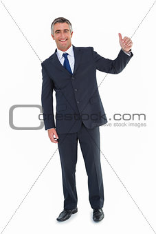 Smiling businessman posing with thumbs up