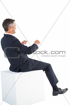 Smiling businessman sitting on a cube