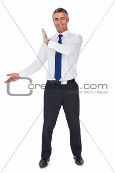 Smiling businessman in suit showing