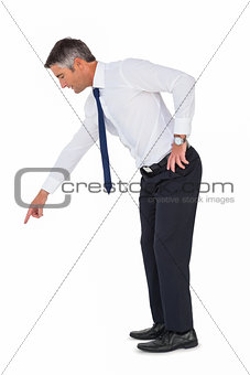 Businessman bending and pointing something down
